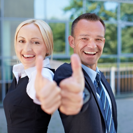 consent: Two happy successful business people holding their thumbs up