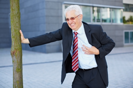 Business man getting a heart attack and holding hand to his chest Stock Photo - 15784009