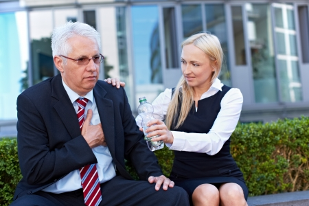 palpitations: Woman offering exhausted senior business man a bottle of water