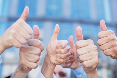 high up: Cheering business people holding many thumbs thumbs up