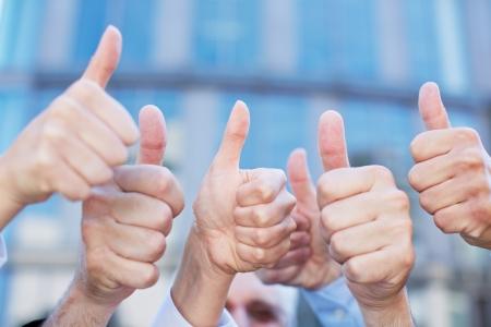 Juichende mensen uit het bedrijfsleven houden veel duimen thumbs up Stockfoto