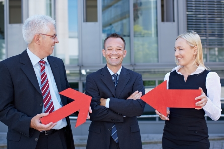 recommendation: Two business people pointing with red arrows at their smiling manager