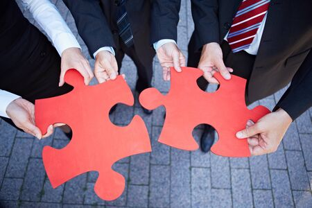 fitting: Business team hands holding two oversized red jigsaw puzzle pieces Stock Photo