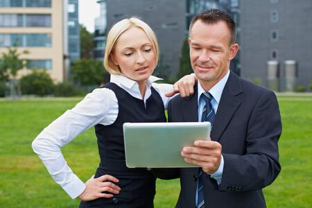 Business manager and assistant working with tablet PC outside photo