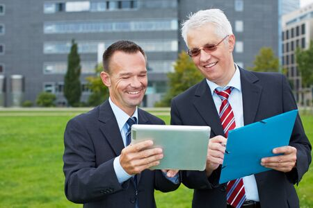 Two business people outside looking at a tablet computer Stock Photo - 15812756