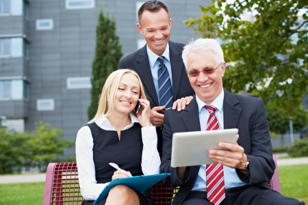 Three happy business people working outside with tablet computer photo