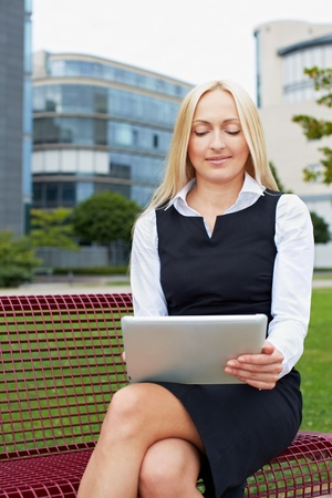 Attractive business woman with tablet computer on a park bench Stock Photo - 15812754