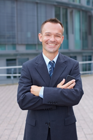 Happy business man with arms crossed outside of his office Stock Photo - 15812761