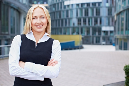 Smiling business woman with her arms crossed outside the office photo