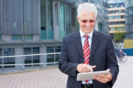 trabajo social: Mayores hombre de negocios sonriente mirando tablet PC en la mano