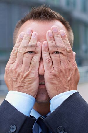 blind people: Business man with eyes on his hands over his face
