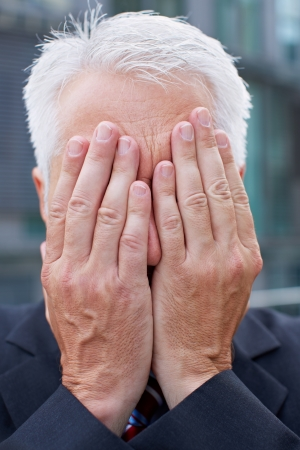 hide: Elderly business man covering his face with both hands Stock Photo