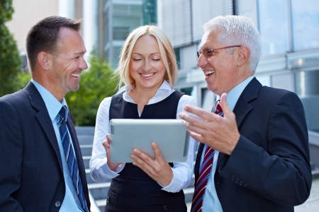 Business team talking and working with tablet computer outside photo