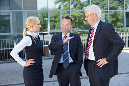 Two business people listening to the speech of a manager photo