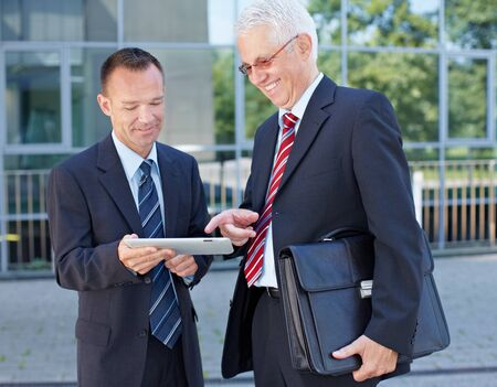Two happy business men using a tablet computer outside the office Stock Photo - 15812768