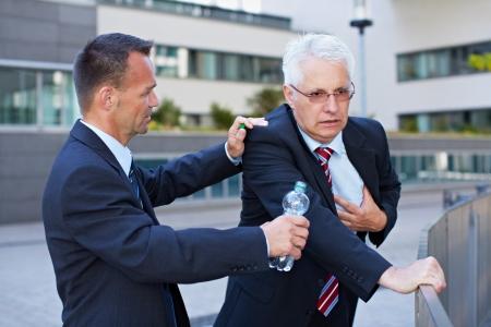 primeros auxilios: Hombre de negocios ayudando a senior con infarto de miocardio con una botella de agua