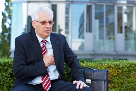 Senior business man with aching heart holding his chest Stock Photo - 15812752