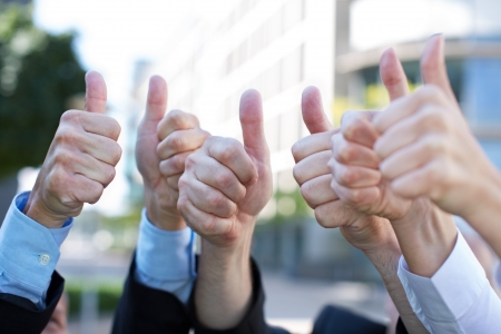 consent: Business team outside the office holding many thumbs up