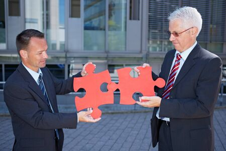 symbolized: Business people solving a problem symbolized with two red jigsaw puzzle pieces Stock Photo