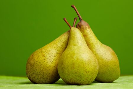 ripeness: Thre pears (Pyrus) leaning in front of a green background