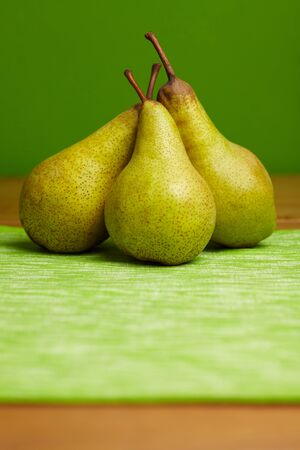 ripeness: Three pears arranged in front of a green background