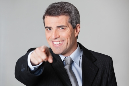 employee satisfaction: Smiling elderly business man showing I Want You gesture