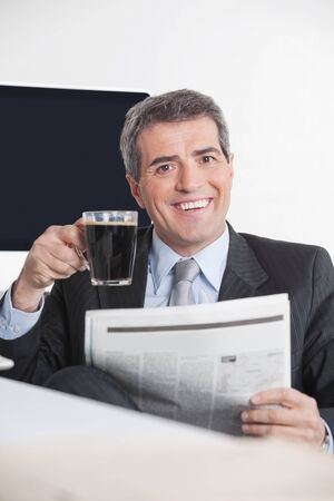 Happy manager sitting with newspaper and coffee at his desk in the office photo