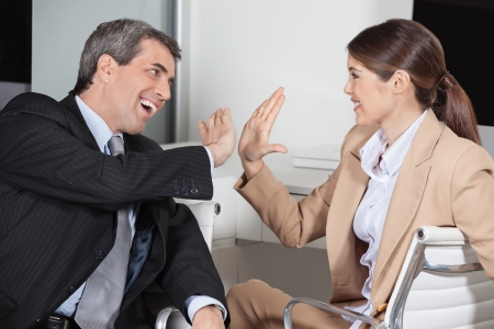 Manager and employee in the office giving high five to each other photo