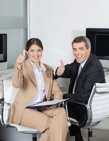 Two happy business people in the office holding their thumbs up Stock Photo - 16128632