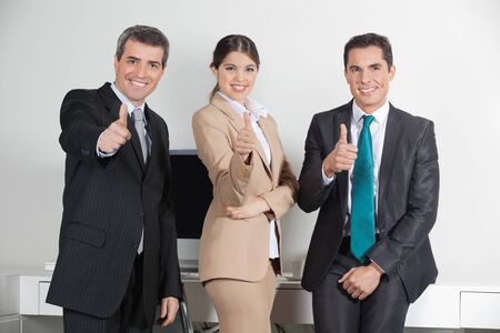 Happy successful business team in the office holding their thumbs up Stock Photo - 16128646