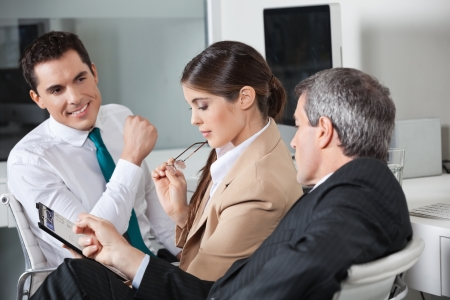 Three business people planning a capital investment in the office Stock Photo - 16128655