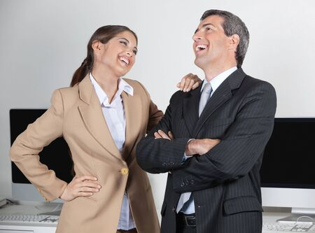 Happy manager and secretary laughing about a joke in the office Stock Photo - 16128651