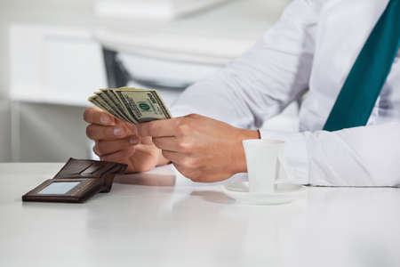 Manager counting a bunch of dollar bills in his office Stock Photo - 16128630