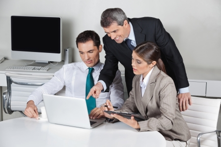 Successful business team working on laptop computer in the office photo
