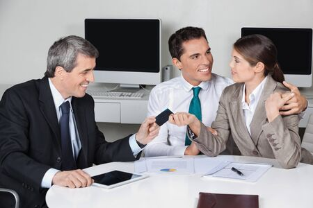 Consultant in his office offering business card to couple  Stock Photo - 16128635