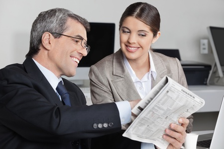 assistent: Smiling business man showing his assistent a newspaper story in the office