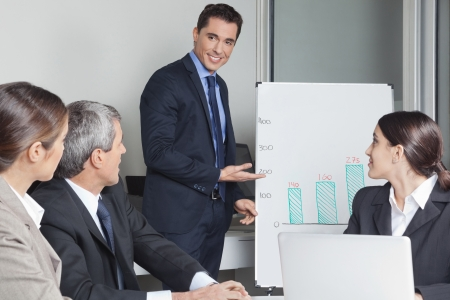 Business man in a office presentation showing sales data on a whiteboard Stock Photo - 16128643