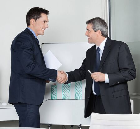 trust people: Two happy successful business partner shaking hands in the office