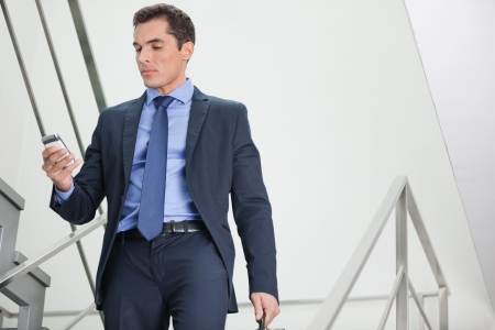 go inside: Manager in staircase looking for network coverage with his smartphone Stock Photo