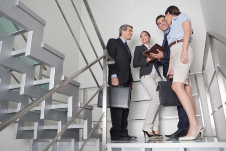 Business team talking to each other in office stairway photo