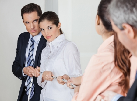 string together: Many business people pulling on a string in the office Stock Photo