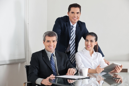 Smiling business team with laptop computer and clipboard in the office Stock Photo - 16128645