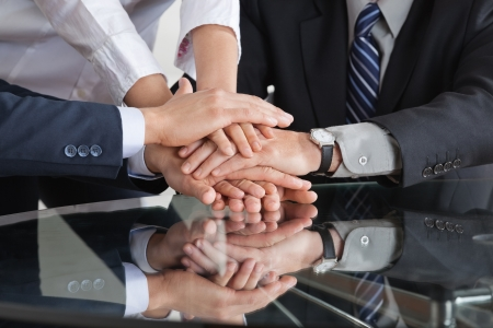 team spirit: Many business people stacking hands to a pile