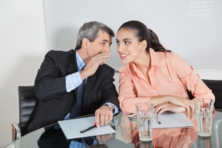intrigue: Manager whispering a secret into the ear of a businesswoman
