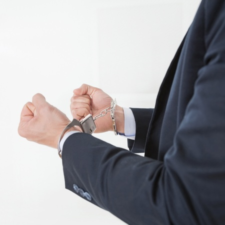 Businessman in handcuffs getting arrested for white collar crimes Stock Photo - 16128599