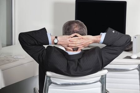 lean back: Relaxed manager at his desk leaning back in the office Stock Photo