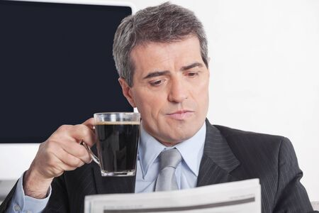 Elderly business man reading a newspaper while drinking a cup of coffee Stock Photo - 16166183