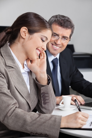 Happy attractive business woman taking notes in the office Stock Photo - 16166191