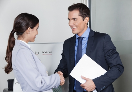 Business man and woman giving handshake in the office photo