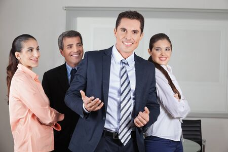 Happy businessman with his team in the office Stock Photo - 16166186